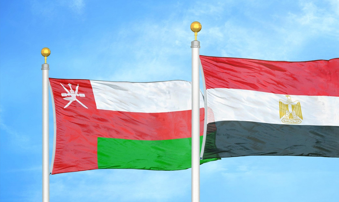 oman and egypt two flags on flagpoles and blue sky